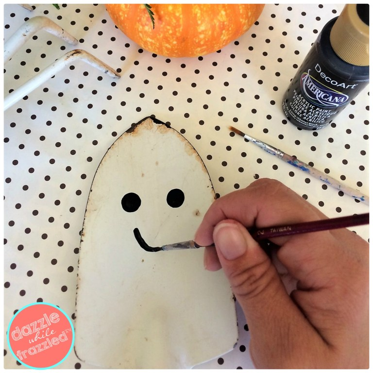 Paint a friendly smile onto a Halloween ghost using an old garden shovel for DIY Halloween home decoration.