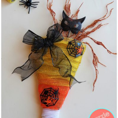 Decorate your front door for Halloween with DIY candy corn wreath made with orange, yellow and white tulle ribbon.