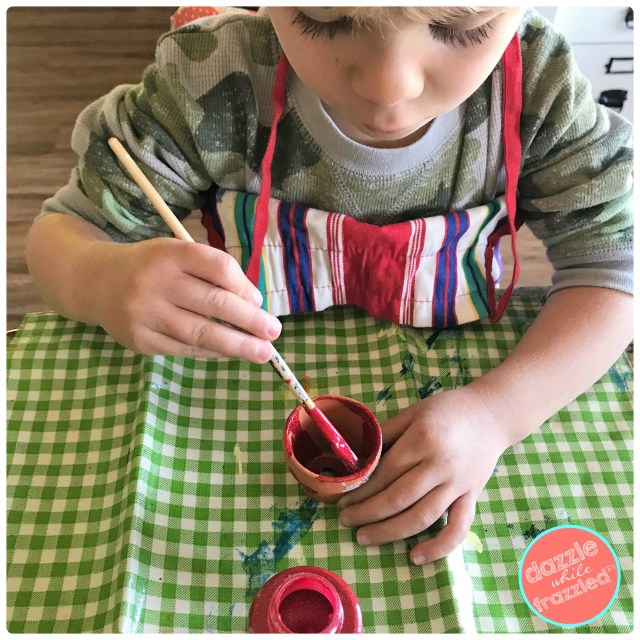 Give the kids craft acrylic paints for DIY Christmas tree ornaments using mini clay flower pots and grosgrain ribbon to hang.