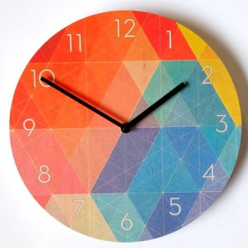 Mid century geometric wall clock with colored triangles mainly in greens, teals, oranges, dust pinks.