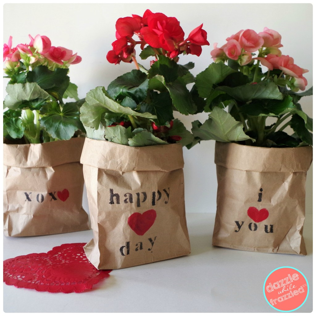 Gift a potted plant or cut flowers in DIY brown paper bags with personalized stenciled messages. Easy, cheap Valentine's Day craft.