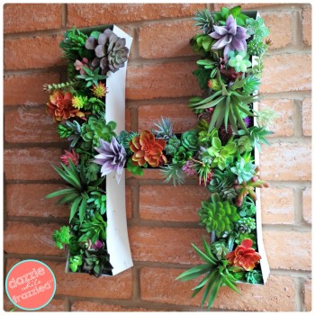 DIY vertical wall planter monogram sign made from vintage large marquee letter and filled with faux succulents.