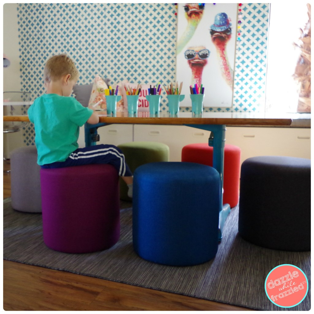 Give the kids a place to color and play games with DIY retro schoolhouse table with colorful ottoman orbs to sit on.