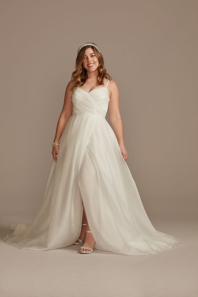 Bride wears pleated organza A-line wedding dress with slit