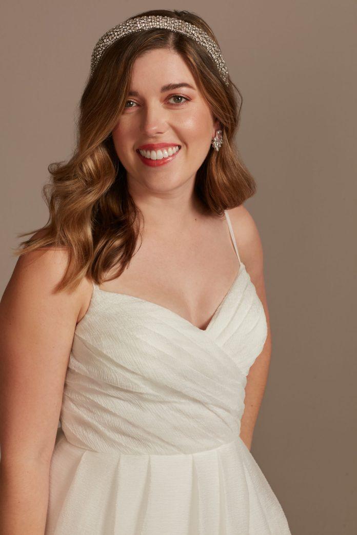Bride wears pleated organza A-line wedding dress with slit