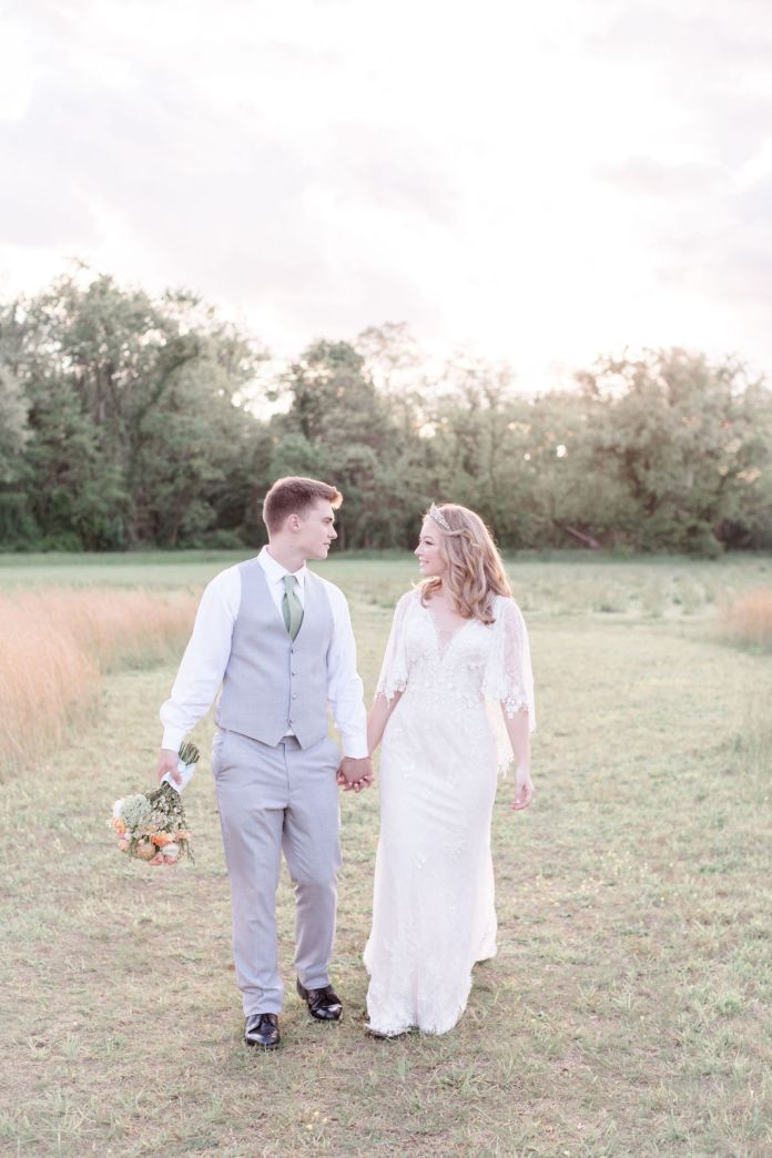 Bride and groom looking at each other hand in hand in a field at a dreamy spring wedding