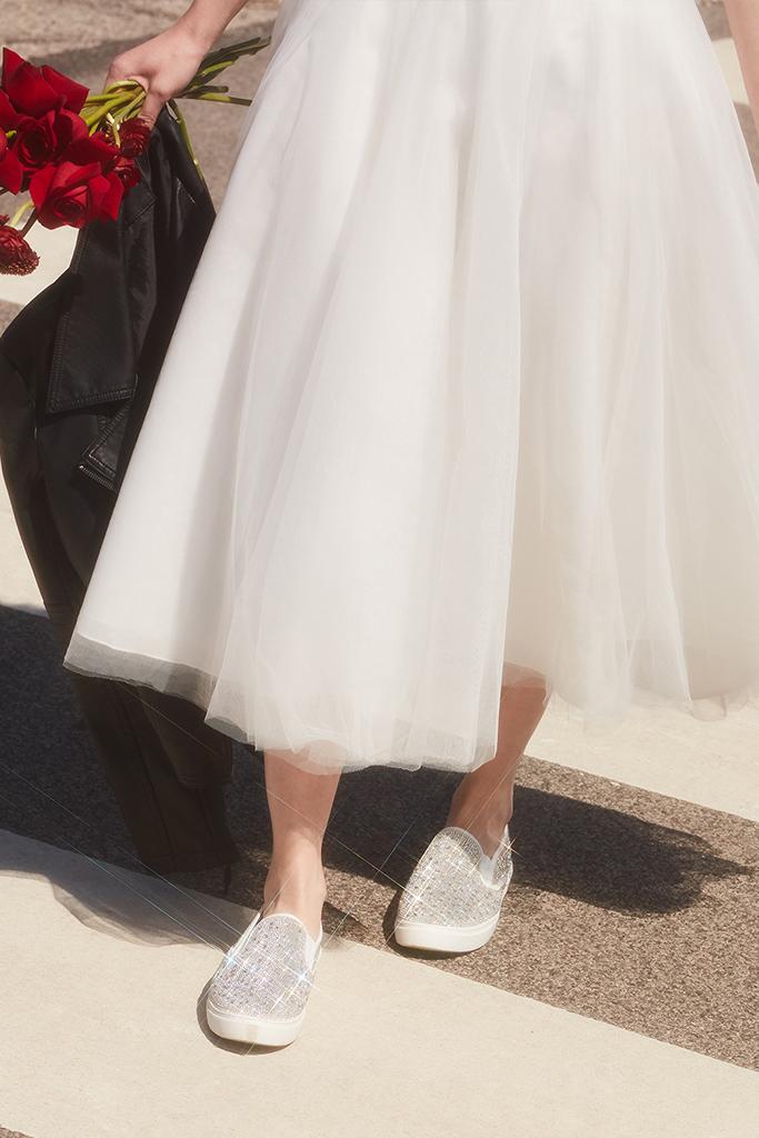 Bride walking down the city street in crystal sneakers