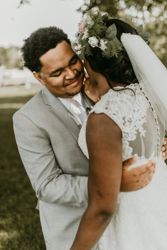 Bride and groom embrace at a rustic outdoor wedding