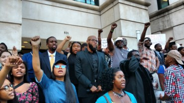 6:13pm: The peaceful protest marched to police headquarters on Trade Street for more chanting. (David Boraks/WFAE)