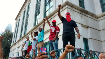 6:12pm: Protesters stood on a wall in front of police headquarters. (David Boraks/WFAE)