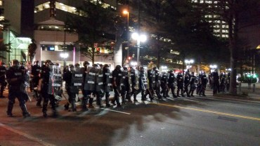 8:52pm: Police walked down Trade Street toward the Omni Hotel in downtown Charlotte 9/21/16 after violence broke out during protests over the killing of Keith Scott. (David Boraks/WFAE)