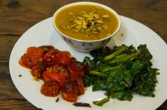 FLATBUSH BROOKLYN - January 4, 2017: Attempting to eat healthier meals in the new year. Vegan butternut squash soup with pumpkin seeds, roasted cherry tomatoes, and sauteed beet greens.