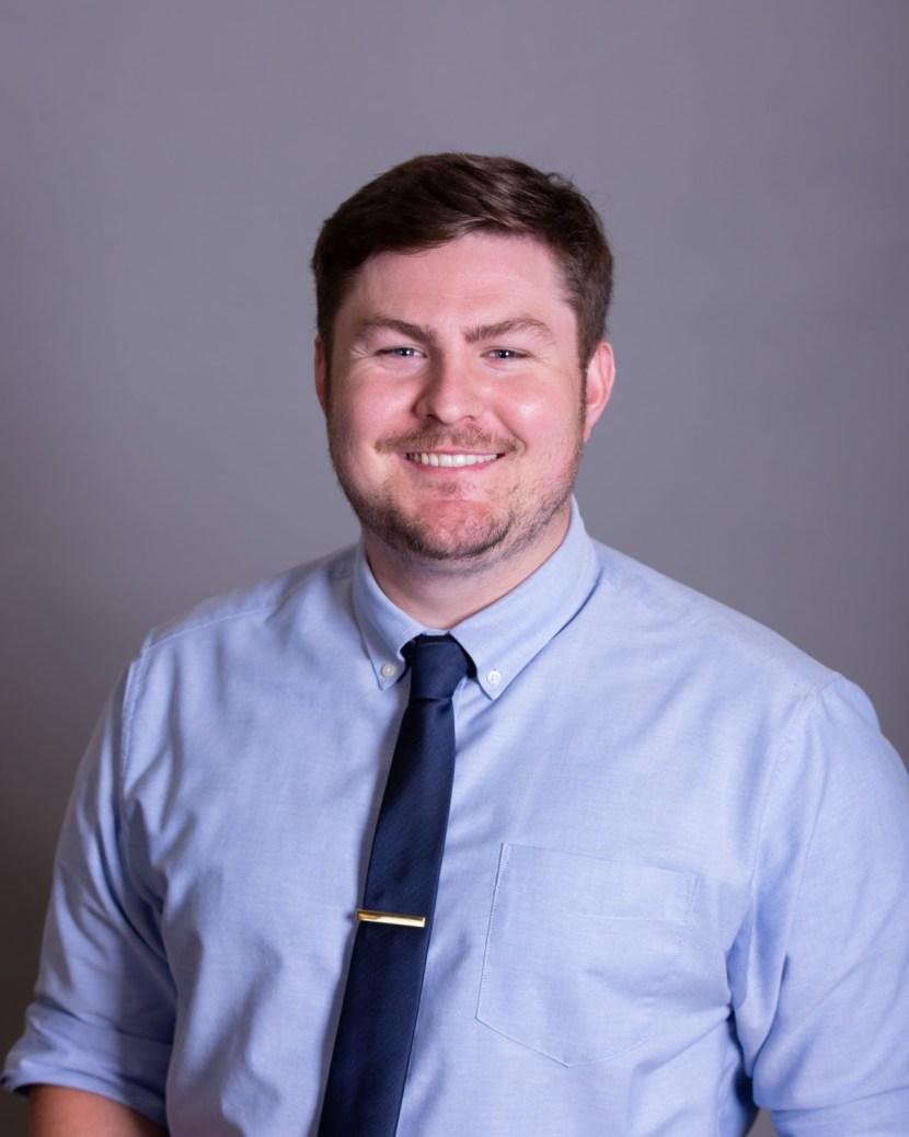 Headshot of Sean Maiwald, in officewear, smiling broadly, gray gradient background.
