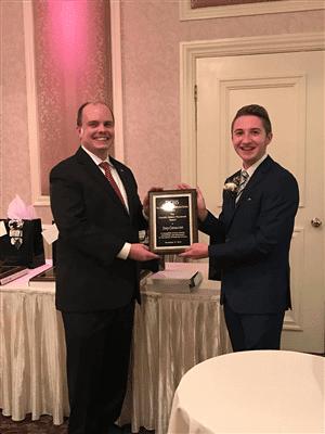 Joey Cavaccini receives the award from County Historian Will Tatum.