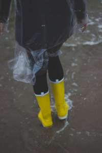 clear rain poncho and yellow galoshes
