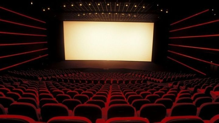 Captioned Movies at Local Theaters Movie theater with rows of seats and a large rectangular screen as wide as  the theater