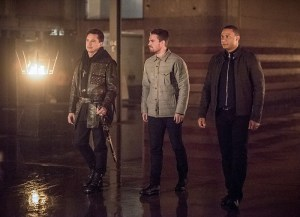 "Arrow -- ""Sins of the Father"" -- Image AR413b_0007b.jpg -- Pictured (L-R): John Barrowman as Malcolm Merlyn, Stephen Amell as Oliver Queen, and David Ramsey as John Diggle -- Photo: Dean Buscher/ The CW -- © 2016 The CW Network, LLC. All Rights Reserved."