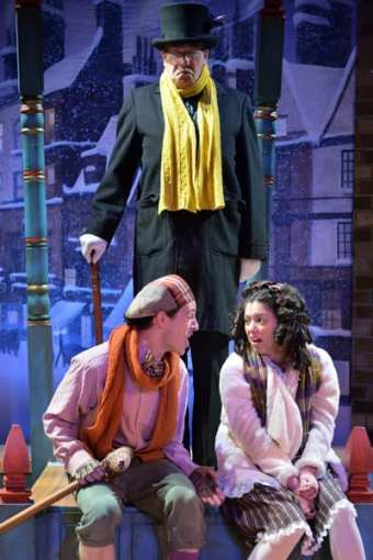 Chris Dinolfo  as Tiny Tim, Brittany Martz as Charlotte and (standing)  Conrad Feininger as Scooge. (Photo: Bruce Douglas)