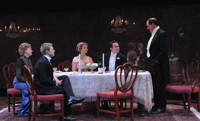 Deborah Hazlett as Sybil Birling, Sophie Hinderberger as Sheila Birling, Jamison Foreman as Gerald Croft, Bruce Randolph Nelson (standing) as Arthur Birling and Josh Adams as Eric Birling, An Inspector Calls at Everyman Theatre (Photo: Stan Barouh)