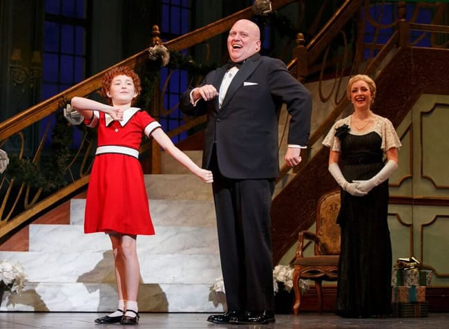 (l-r) Heidi Gray as Annie, Gilgamesh Taggett as Oliver Warbucks, and Chloe Tiso as Grace Farrell in Annie at the National Theatre (Photo: © Joan Marcus)