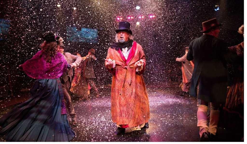 David Bosley-Reynolds as Ebenezer Scrooge in A Christmas Carol: The Musical with Noah as Tiny Time (far right). (Photo: Jeri Tidwell Photography)
