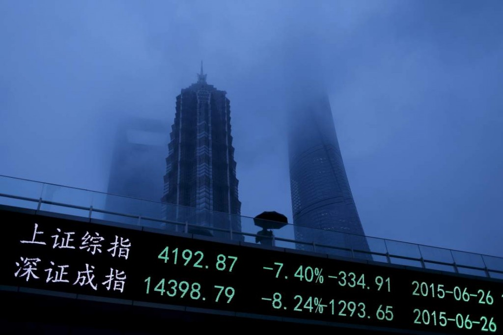 A man walks past an electronic board showing the benchmark Shanghai and Shenzhen stock indices, on a pedestrian overpass at the Pudong financial district in Shanghai, China, June 26, 2015. Chinese stocks plunged over 7 percent on Friday, with one key index recording its biggest fall since 2008, hit by tight liquidity conditions ahead of the quarter-end and uncertainty over the central bank's easing policy. REUTERS/Aly Song TPX IMAGES OF THE DAY - RTX1HVU8