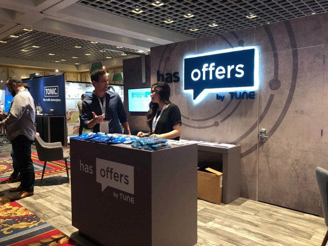 Two HasOffers reps chat in their booth at Affiliate Summit West 2019