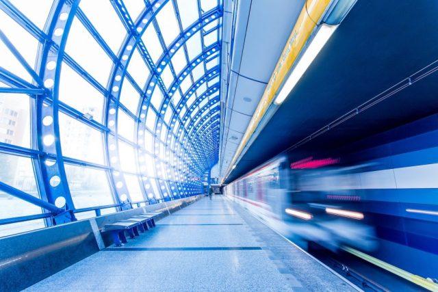 A commuter train passes a platform