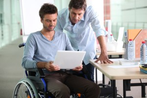 Individual in a wheelchair holding a laptop.