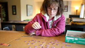 woman sorts puzzle pieces in her home
