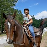 Photo of a girl riding a horse