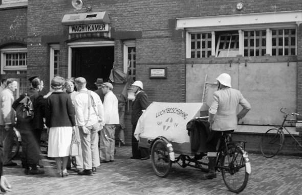 """Foto Hans Sibbelee, Collectie Nederlands Fotomuseum. Een gewonde van het zgn. """"Dam-incident', waarbij enkele leden van de Kriegsmarine ineens het vuur openden op de feestende menigte op de Dam te Amsterdam, wordt met een tot ambulance omgebouwde bakfiets van de Dienst Luchtbescherming naar het Binnengasthuis gebracht (7 mei 1945)"""