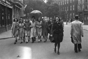 Mensen lopen in feeststemming naar de Dam om de bevrijders te verwelkomen.