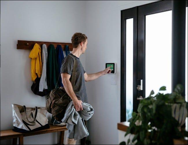 Mann mit Touchscreen-Panel vor der Haustür