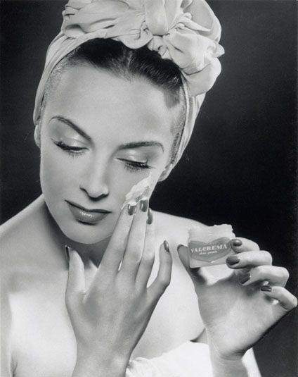 Woman applying skin cream to her face.
