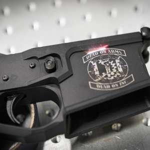 A DOA logo being engraved on a gun.