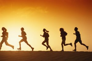 People running in desert at dusk, side view