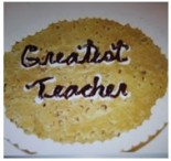 Giant chocolate chip cookie with Greatest Teacher written in icing