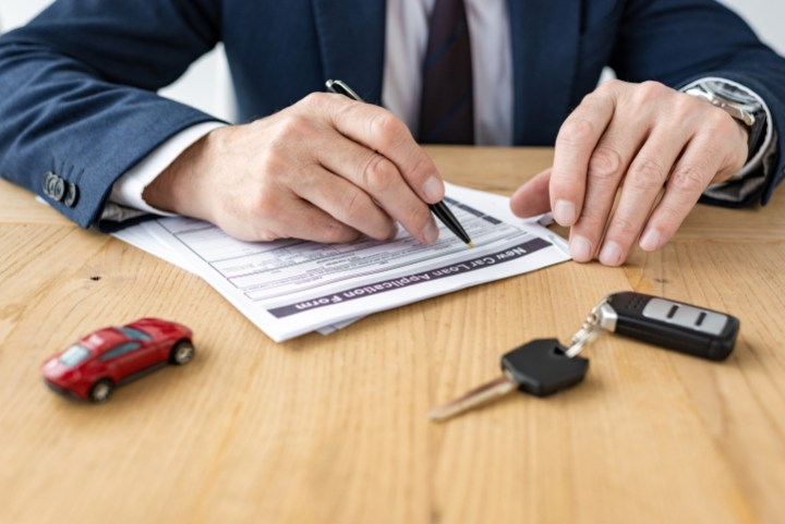 selective focus of car dealer holding pen near contract, toy car and car key