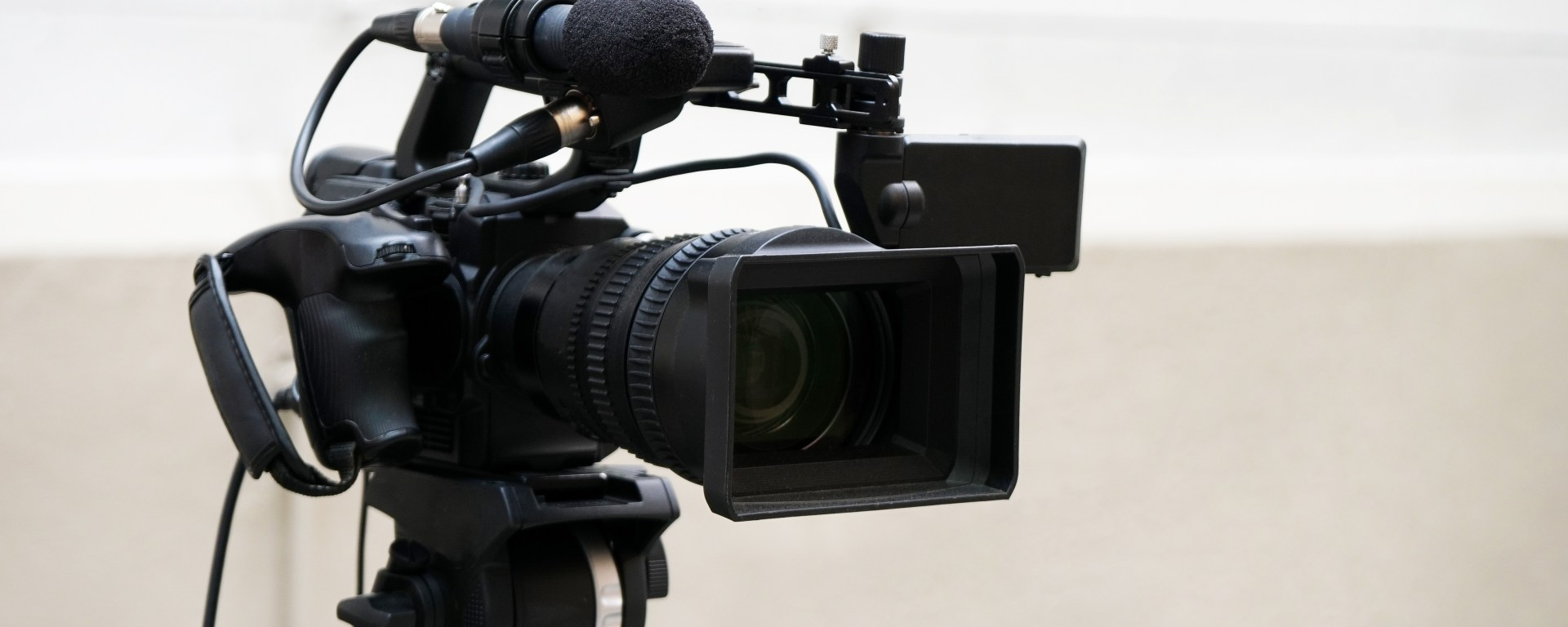 professional digital video or movie camera with microphone on tripod