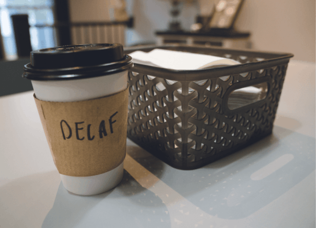 A to-go coffee cup with 'decaf' written on the side of it