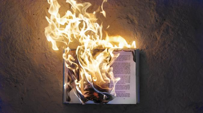 A book burns on the ground, something I wanted to do a lot with reading OCD!