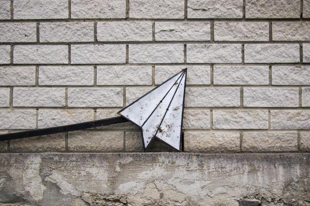 Paper airplane art on a brick wall