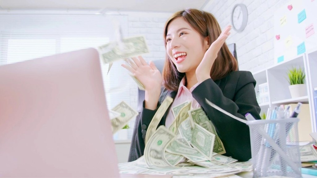woman sitting at laptop with money