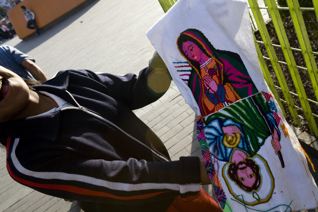 A young girl sells images of the Virgin of Guadalupe at the Insurgentes metro station in Mexico City.