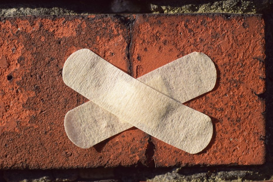 two baind-aids crossed to make an x over a crack in a brick wall.