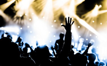 crowd with hands raised at a live music concert