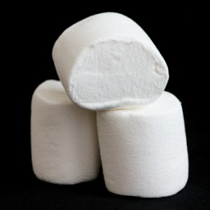 Three marshmallows stacked and isolated on black.