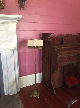 The secret room entrance was on the right side of the fireplace behind the organ.