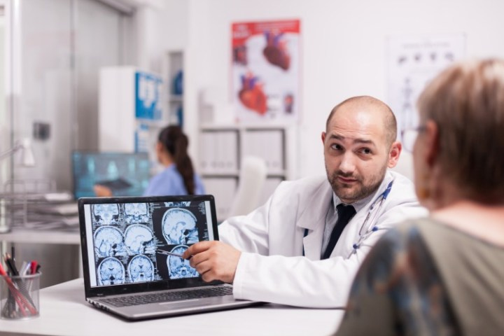 doctor discusses alzheimer's diagnosis with patient using x-rays of brain on a laptop
